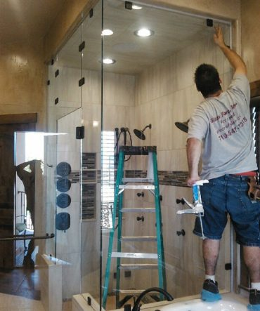 Glass Force employees installing shower glass doors in residential Pueblo home